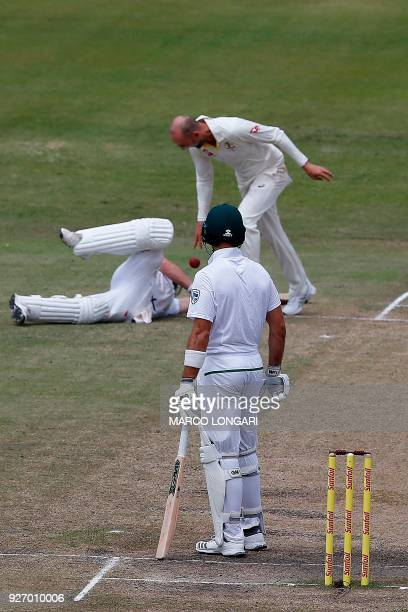 Australian bowler Nathan Lyon drops the ball on South African batsman AB de Villiers after running him out during the fourth day of the first Test...