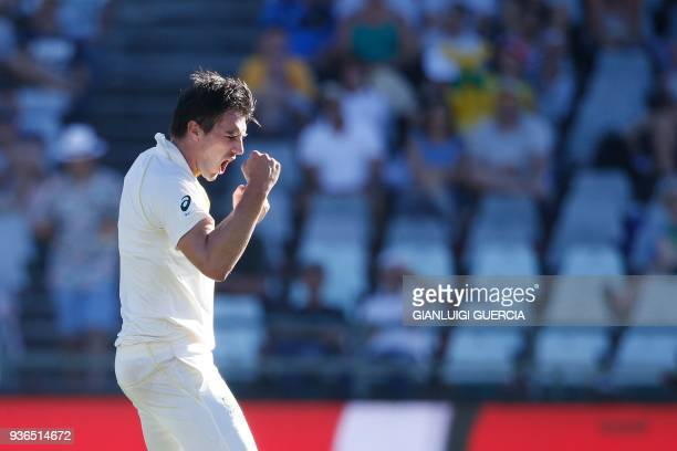 Australian bowler Pat Cummins celebrates the dismissal of South African batsman Temba Bavuma during the first day of the third Test cricket match...