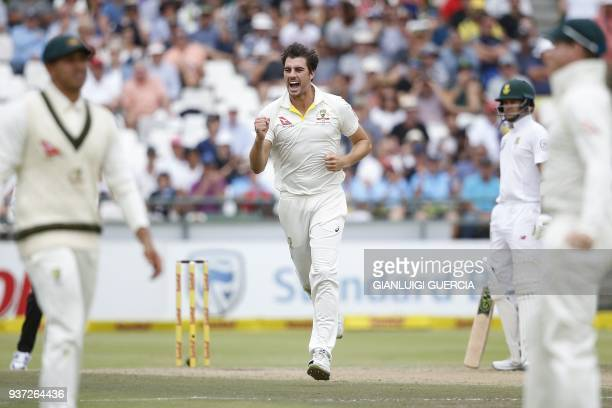 Australian bowler Pat Cummins celebrates the dismissal of South African batsman Dean Elgar during the third day of the third Test cricket match...