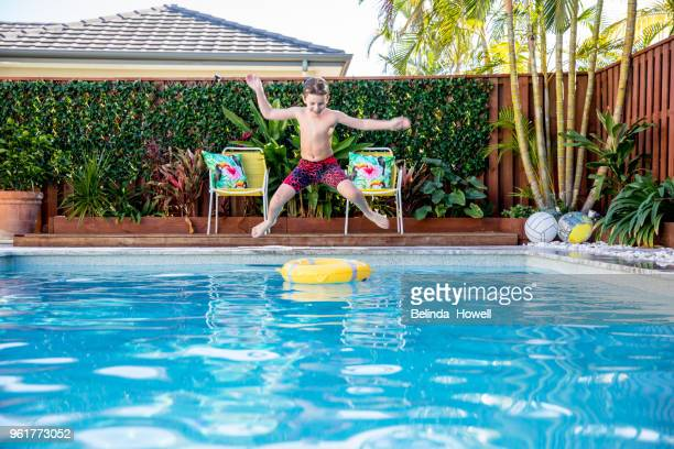 Australian boy enjoys swimming and playing in backyard pool