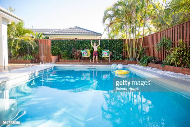 australian boy enjoys swimming and playing in backyard pool - kids pool games stock pictures, royalty-free photos & images