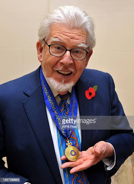 Australian broadcaster and artist Rolf Harris holds the Officer of the Order of Australia presented by the High Commissioner John Dauth at Australia...