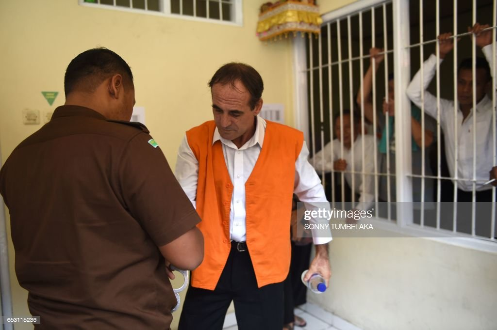 Australian businessman Giuseppe Serafino (R) is escorted by an Indonesia prosecutor from a holding cell to his trial at a court in Denpasar on Indonesia's resort island of Bali on March 14, 2017. Serafino is charged with using, possessing and transporting hashish after allegedly being caught in possession of small amounts of the drug in October 2016. / AFP PHOTO / Sonny TUMBELAKA