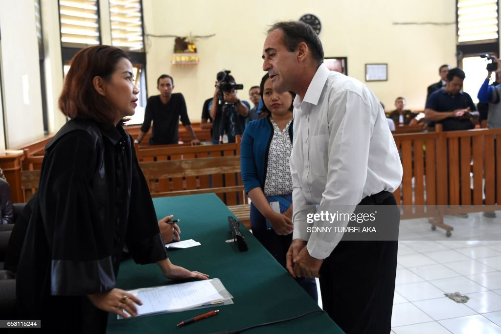 Australian businessman Giuseppe Serafino (R) speaks with his lawyer after his trial at a court in Denpasar on Indonesia's resort island of Bali on March 14, 2017. Serafino is charged with using, possessing and transporting hashish after allegedly being caught in possession of small amounts of the drug in October 2016. / AFP PHOTO / Sonny TUMBELAKA