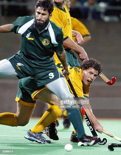 Australian captain Brent Livermore gets a shot away on goal in front of Pakistan defender Tariq Imran during their match in Sydney 05 June 2003...