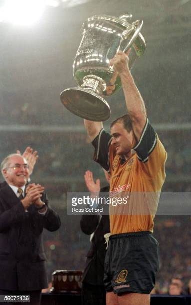 Australian captain David Wilson holds the Bledisloe Cup aloft as he is applauded by Australian PM John Howard following their 287 win over the All...
