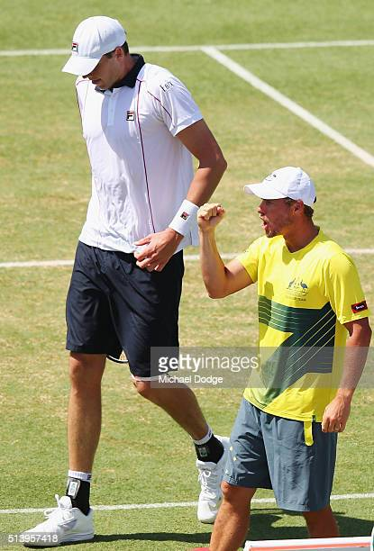 Australian Captain Lleyton Hewitt celebrates next to John Isner of the USA as Bernard Tomic of Australia wins the third set in his match against John...