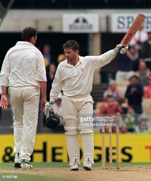 Australian captain Mark Taylor salutes his home crowd as he is congratulated by English pace seamer Angus Fraser for his century during the final...