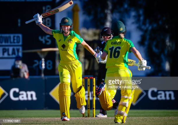Australian captain Meg Lanning raises bat to celebrate reaching her century after taking the winning runs on the last ball of play during the second...