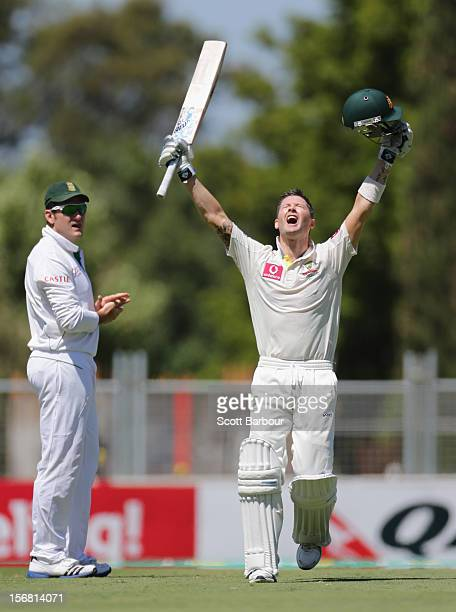 Australian captain Michael Clarke celebrates as he reaches his century as South African captain Graeme Smith looks on during day one of the 2nd Test...