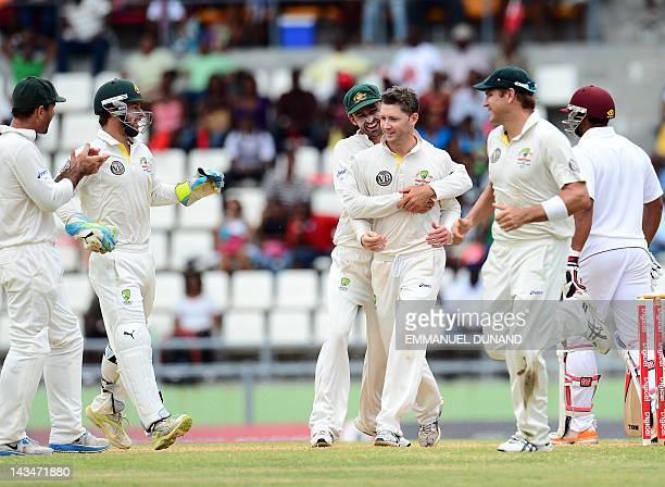Australian captain Michael Clarke is congratulated after taking the wicket of West Indies batsman Ravi Rampaul during the fifth day of the third test...
