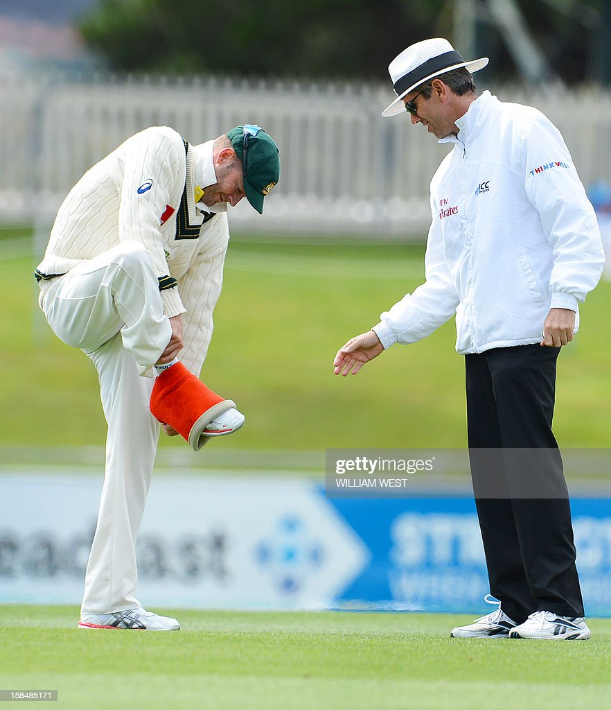 Australian captain Michael Clarke (L) removes a compression bandage as umpire Nigel Llong (R) looks on on the final day of the first cricket Test match, in Hobart on December 18, 2012. AFP PHOTO/William WEST IMAGE