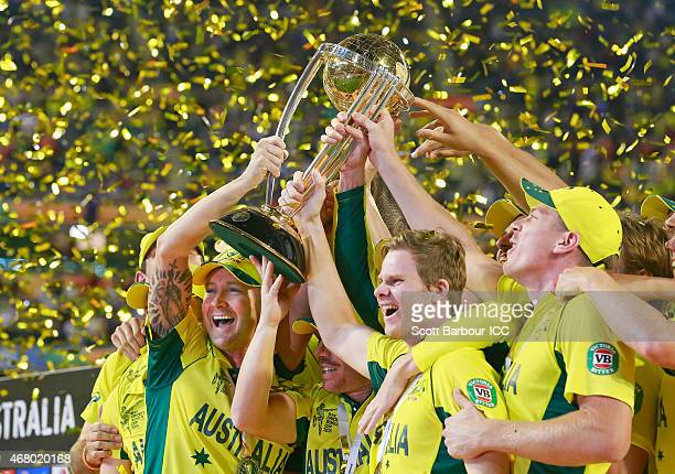Australian captain Michael Clarke Steven Smith and Australian players celebrate with the World Cup trophy as they celebrate after Australia won the...