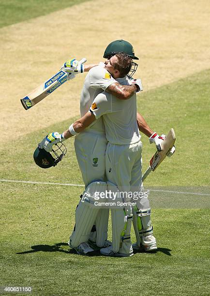 Australian captain Steve Smith celebrates scoring a century with team mate Mitchell Johnson during day three of the 2nd Test match between Australia...