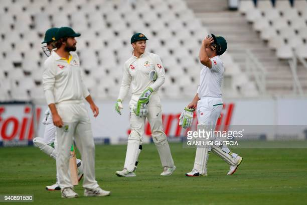 Australian Captain Tim Paine South African batsmen Dean Elgar and Fat du Plessis leave the field as play is suspended due to bad light on the fourth...