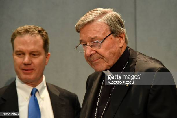 Australian Cardinal George Pell flanked by Vatican press office director Greg Burke arrives to deliver a statement at the Holy See Press Office...