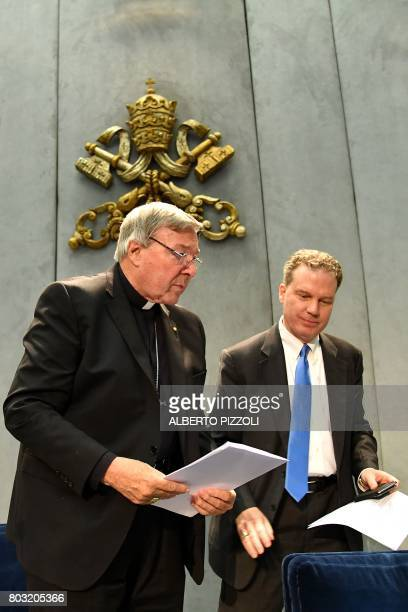 Australian Cardinal George Pell flanked by Vatican press office director Greg Burke leaves after he delivered a statement at the Holy See Press...