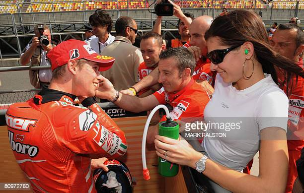 Australian Casey Stoner from the Ducati Team celebrates with team members and his wife after qualifying in third position at the Grand Prix of China...