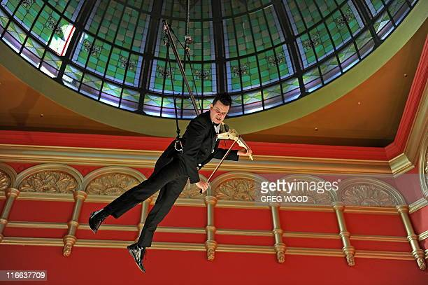 Australian classical musician Shenzo Gregorio plays an electric violin while suspended under the dome of the historic Queen Victoria Building in...