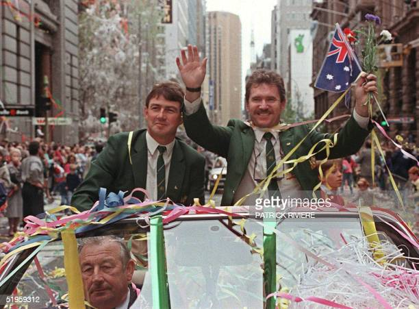 Australian cricket captain Allan Border accompanied by his teammate Geoff Marsh waves the national flag 28 September during a parade to celebrate the...