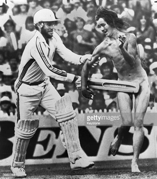 Australian cricket captain Greg Chappell shields a streaker with his bat during the World Series match between Austalia and the West Indies in...