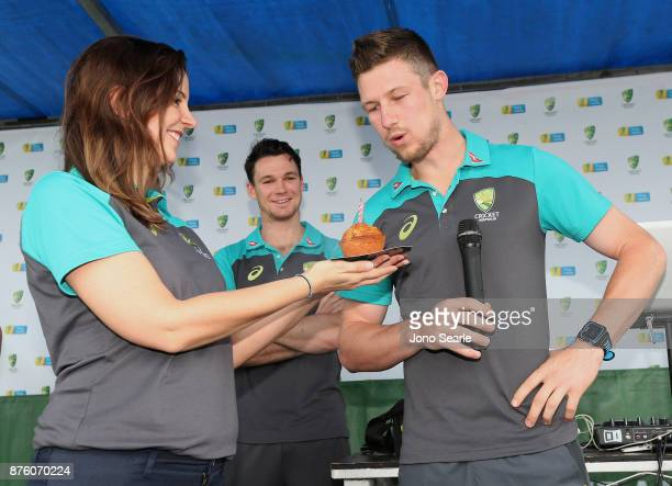 Australian Cricket player Cameron Bancroft blows out a candle as he is wished happy birthday as team mate Peter Handscomb looks on as they attend the...