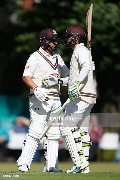 Australian cricketer Aaron Finch of Surrey is congratulated by teammate Steven Davies after scoring 50 runs during the Specsavers County Championship...