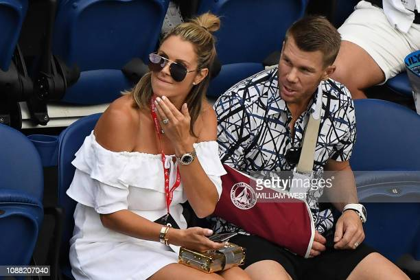 Australian cricketer David Warner and his wife Candice watch Serbia's Novak Djokovic play against France's Lucas Pouille during their men's singles...
