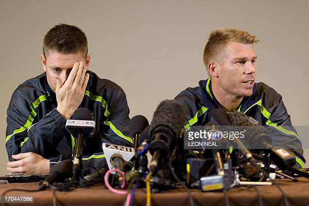 Australian cricketer David Warner answers questions from the media as he sits beside team captain Michael Clarke during a press conference in central...