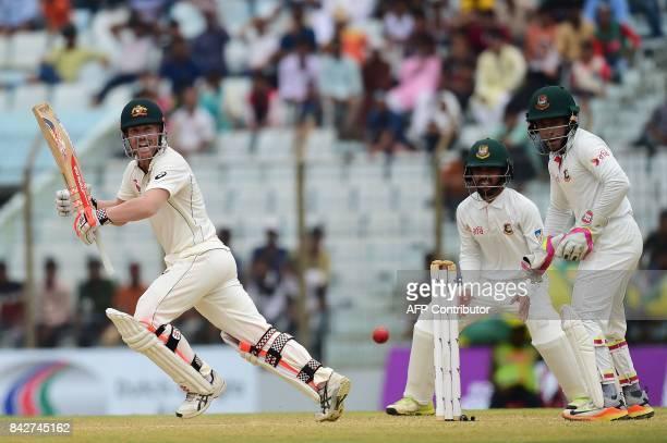 TOPSHOT Australian cricketer David Warner plays a shot as the Bangladeshi cricket captain Mushfiqur Rahim and Mominul Haque look on during the second...