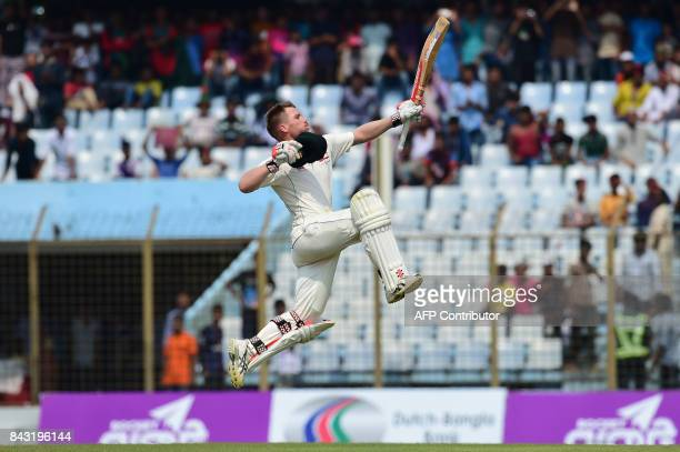 TOPSHOT Australian cricketer David Warner reacts after scoring a century during the third day of the second cricket Test between Bangladesh and...