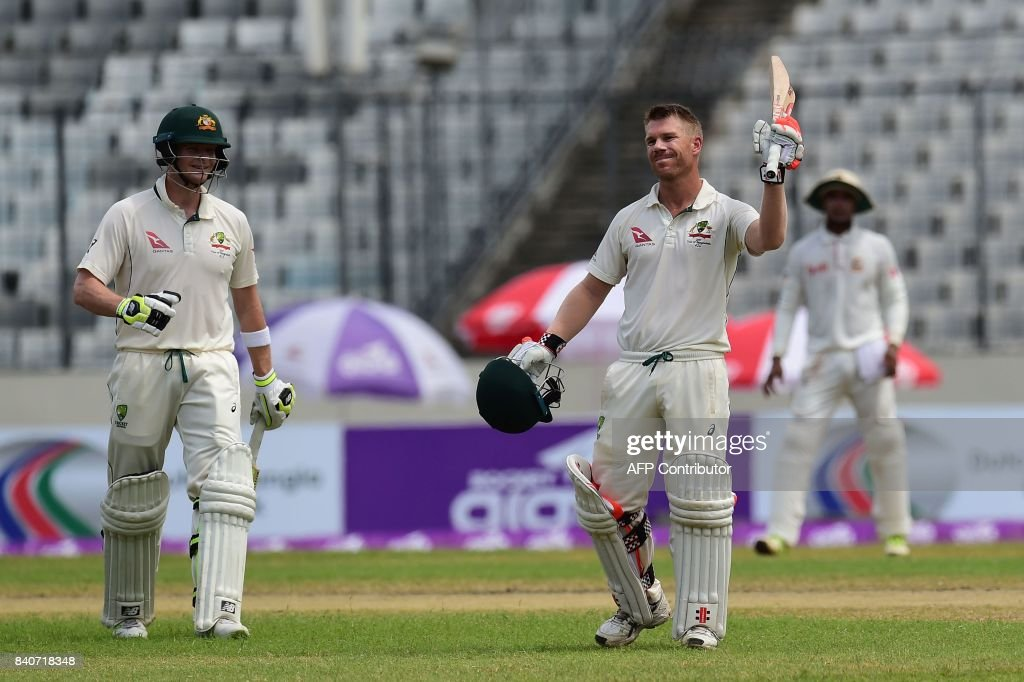 Australian cricketer David Warner (C) reacts as his captain Steven Smith (L) looks on after scoring a century (100 runs) during the fourth day of the first Test cricket match between Bangladesh and Australia at the Sher-e-Bangla National Cricket Stadium in Dhaka on August 30, 2017. / AFP PHOTO / Munir UZ