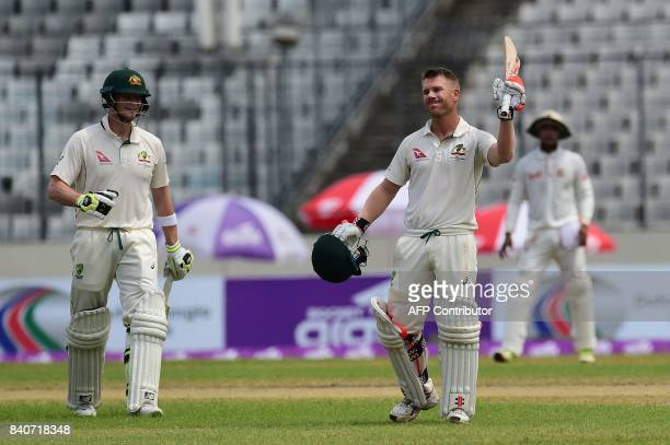 Australian cricketer David Warner reacts as his captain Steven Smith looks on after scoring a century during the fourth day of the first Test cricket...