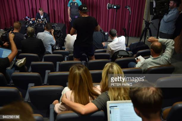 Australian cricketer David Warner speaks as his wife Candice looks on at a press conference at the Sydney Cricket Ground in Sydney on March 31 2018...