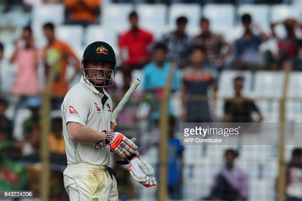 Australian cricketer David Warner walks off the field after being dismissed by Bangladeshi cricketer Mustafizur Rahman during the third day of the...