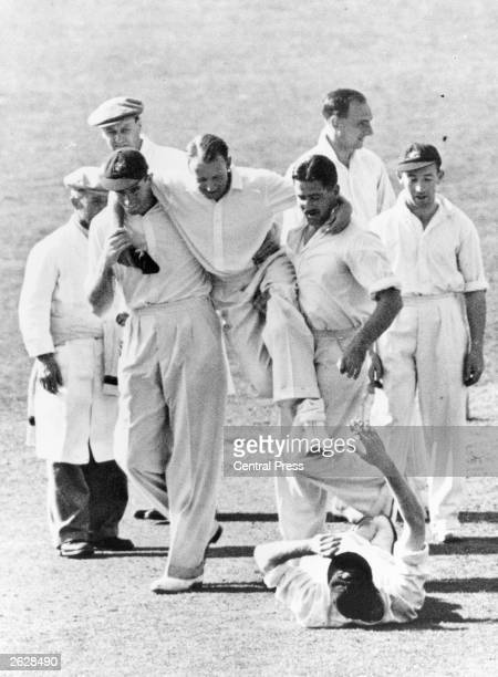 Australian cricketer Don Bradman is carried off after injuring his foot during a Test Match between England and Australia at the Oval London Sir...