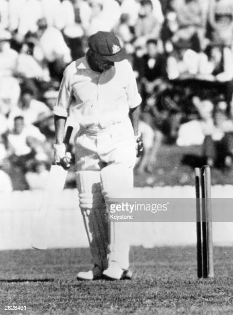 Australian cricketer Don Bradman looking down at the stumps after being bowled out for four during a MCC versus Prime Minister match held in Canberra...