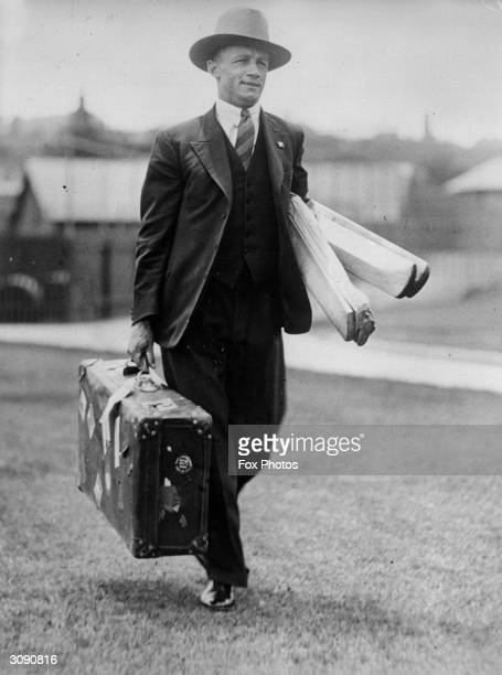 Australian cricketer Donald Bradman arrives for an important match carrying his suitcase and bats.