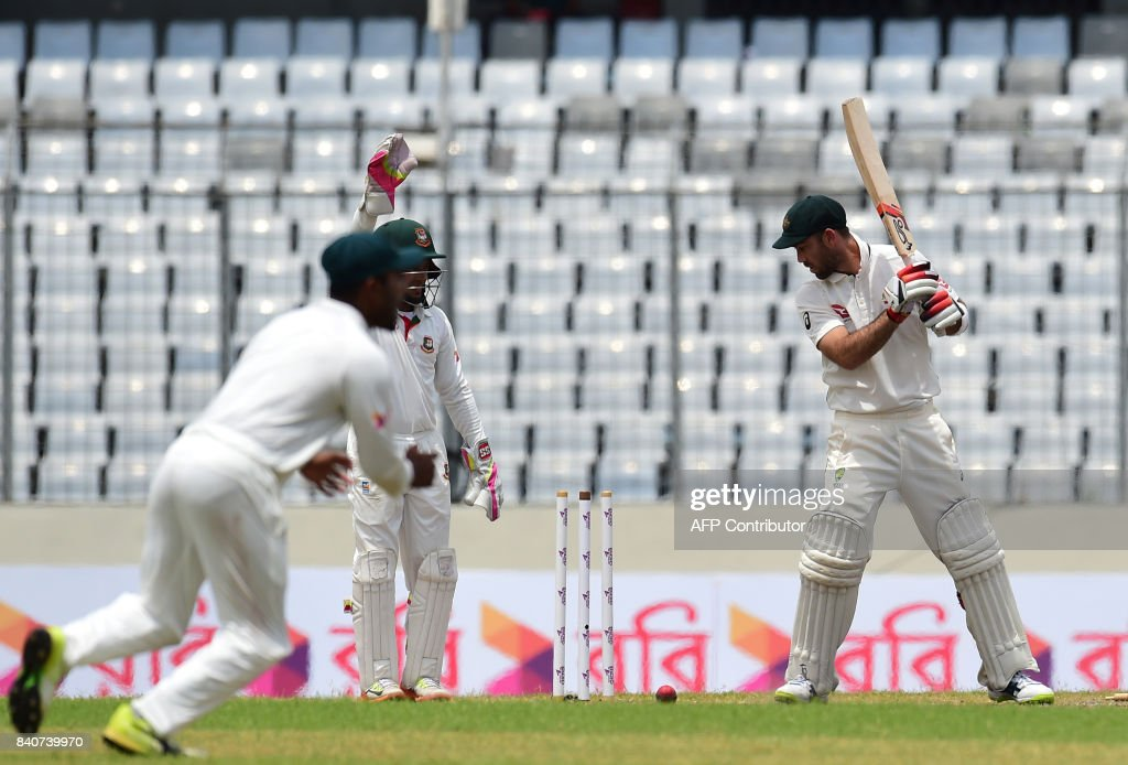 Australian cricketer Glenn Maxwell (R) is bowled out by the Bangladeshi cricketer Shakib Al Hasan during the fourth day of the first Test cricket match between Bangladesh and Australia at the Sher-e-Bangla National Cricket Stadium in Dhaka on August 30, 2017. / AFP PHOTO / Munir UZ