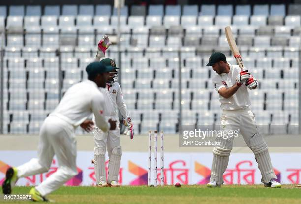 Australian cricketer Glenn Maxwell is bowled out by the Bangladeshi cricketer Shakib Al Hasan during the fourth day of the first Test cricket match...