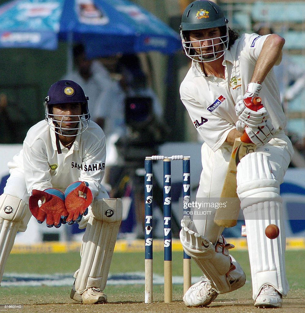 Australian cricketer, Jason Gillespie (R) plays a stroke as Indian wicketkeeper Dinesh Kartik (L) waits with open gloves at the Wankhede Stadium, Bombay, 04 November 2004, on day two of the fourth Test between Australia and India. Australia are chasing India's first innings, all out for 104 runs. AFP PHOTO/Rob ELLIOTT