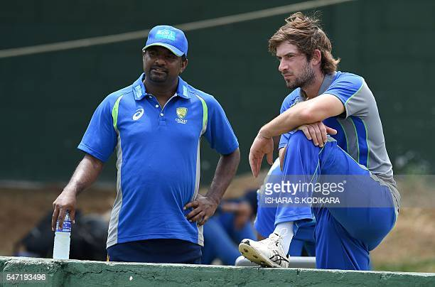 Australian cricketer Joe Burns speaks with Australia's bowling consultant Sri Lankan former cricketer Muttiah Muralitharan during a practice session...