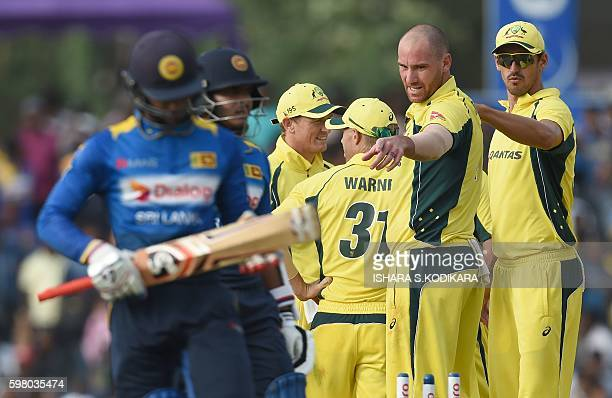 Australian cricketer John Hastings celebrates with teammates after he dismissed Sri Lanka cricketer Dhananjaya de Silva during the fourth One Day...