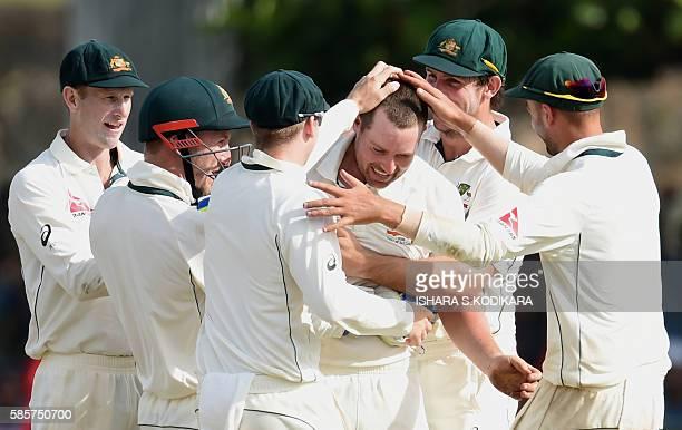 Australian cricketer Jon Holland celebrates with teammates the dismissal of Sri Lankan batsman Dhananjaya de Silva during the first day of the second...