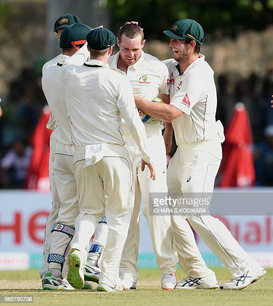 Australian cricketer Jon Holland celebrates with teammates the dismissal of Sri Lankan batsman Dhananjaya de Silva during the first day of the second...