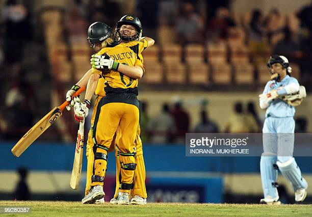Australian cricketer leah Poulton embraces her teammate Jess Cameron after defeating India as Indian wicketkeeper Sulakshana Naik looks on at the end...