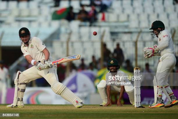 Australian cricketer Matt Renshaw plays a shot as the Bangladeshi cricket captain Mushfiqur Rahim and Mominul Haque looks on during the fourth day of...