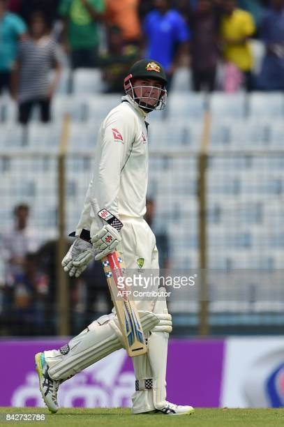 Australian cricketer Matt Renshaw walks off the field after being dismissed by Bangladeshi cricketer Mustafizur Rahman during the second day of the...