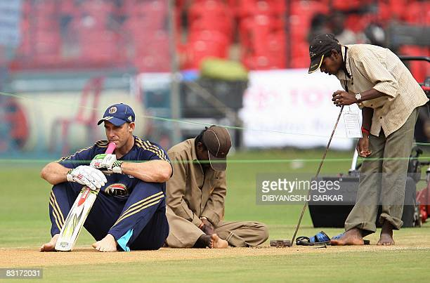 Australian cricketer Matthew Hayden sits on the pitch as groundsmen work around him during a practice session at The Chinnaswamy Stadium in Bangalore...