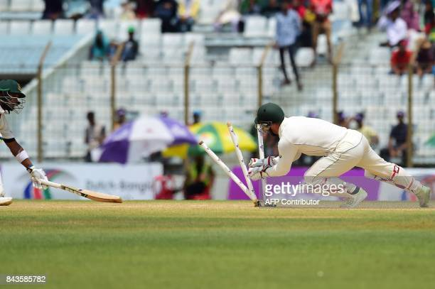 Australian cricketer Matthew Wade breaks the stumps as the Bangladeshi cricketer Sabbir Rahman tries to make the crease during the fourth day of the...